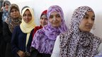Women wait to cast their vote at a polling station in Tripoli (7 Jul 2012)