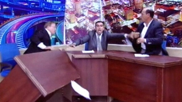 A TV presenter tries to hold back his two guests from fighting