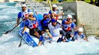Zachary Franklin carrying the Olympic flame on a raft down the Lee Valley White Water Centre