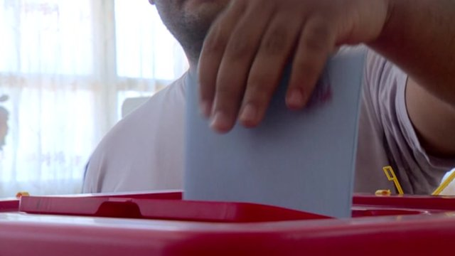 A man putting a voting form in a ballot box