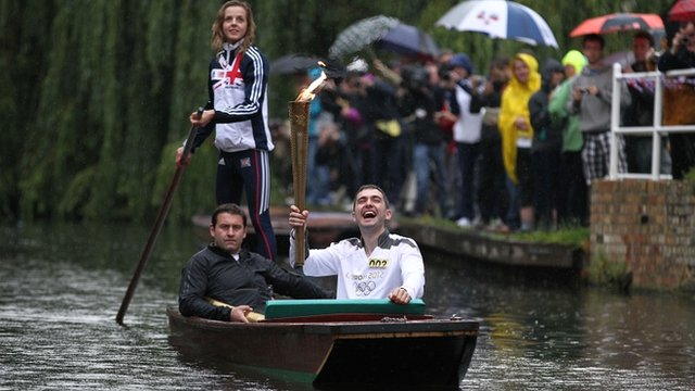 Edward Roberts carries the Olympic Flame on a punt on the River Cam on 8/7/12