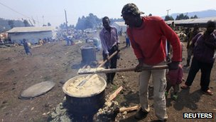 Congolese refugees prepare a meal at the Nyakabande refugee transit camp in Kisoro town