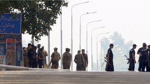 Pakistani army soldiers and police commandos stand on a bridge over the river Chenab after an attack on an army camp in Wazirabad