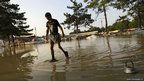A man walks along a flooded playground at the stadium in Krymsk.