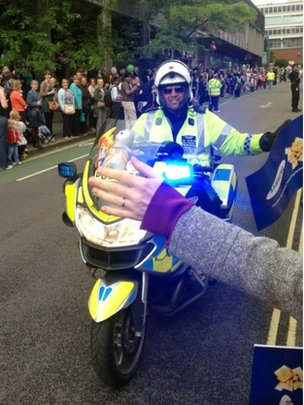 Police biker high fives the crowd