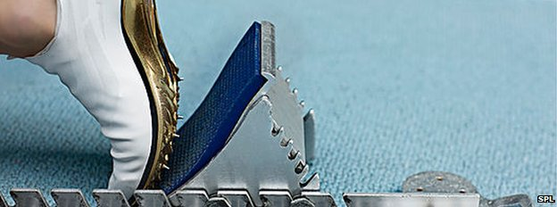 Running shoe with spikes in starting block (Science Photo Library)