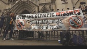 A protester with a banner outside the Royal Courts of Justice