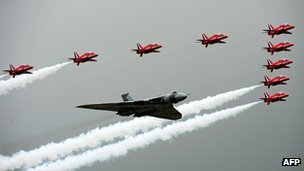 The Red Arrows fly in formation  with a Vulcan bomber