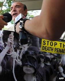Alan Shadrake, a freelance journalist and author displays the campaign poster while talking to reporters outside the Supreme court in Singapore on 27 May, 2011