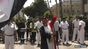 A supporter of President Mohammed Mursi wears and carries an Egyptian flag in front of the parliament building in Cairo