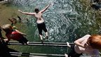 Payton Sehofield, 12, jumps into the Big Wood River from an old train bridge to cool off in Sun Valley, Idaho.