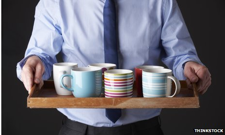 Man carrying tray with mugs 