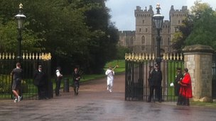 Phillip Wells carries the Olympic flame through Windsor Castle gates, 10 July 2012