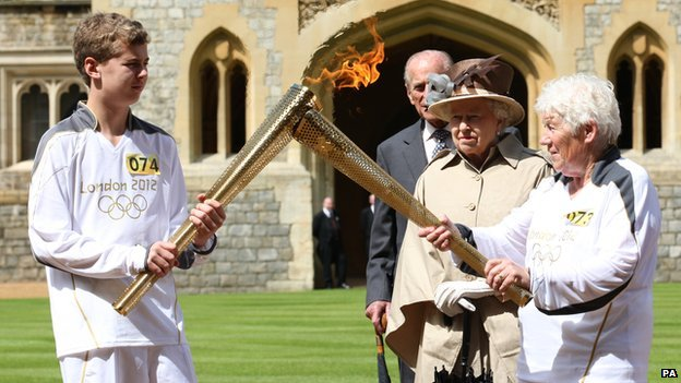 Queen watches as two people pass on the Olympic flame