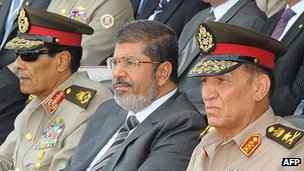 The head of Scaf, Field Marshal Mohammed Hussein Tantawi, President Mohammed Morsi and army chief of staff Gen Sami Enan sit together