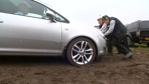 Two people pushing a car in a muddy field