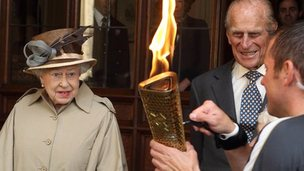 The Queen and Prince Philip watch as the flame is lit.