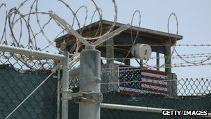 In this image reviewed by the US. Military, a guard looks from a tower, surrounded by barbed wire, above the Camp 4 detention facility, July 23, 2008 at Guantanamo Bay US. Naval Base, in Cuba