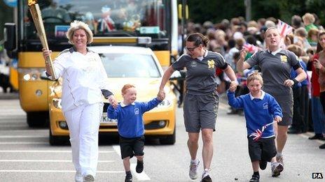 Torchbearer Brenda Heys runs with her two sons