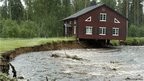 A house, with its foundation washed away, hangs over a rain-swollen creek