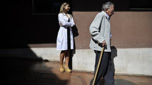 An elderly man walks with a stick next to a woman in a white coat