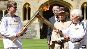 The Queen and Prince Philip watch as the flame is passed on