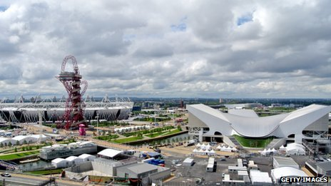 The ArcelorMittal Orbit sculpture standing in front of the Olympic Stadium, with the Aquatics Centre to the right