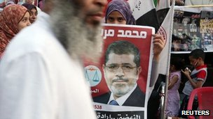 A supporter holds a poster of Egypt&#039;s President Mohammed Mursi at Tahrir Square in Cairo 10 July
