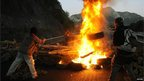 Miners throw tyres onto a barricade on the AP-66 motorway in northern Spain in protest against Spanish subsidy cuts to mining