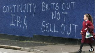 A schoolgirl walks past graffiti in Belfast in May 2000