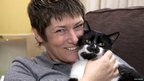 Woman cuddles black and white cat