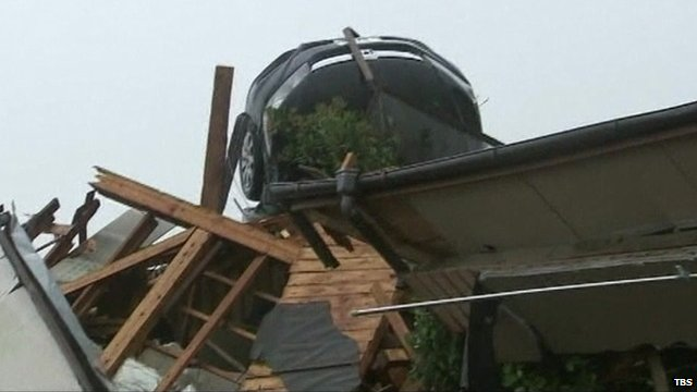 Car stranded on top of house after flooding in Japan