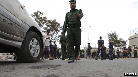 A policeman gestures in Sanaa shortly after a suicide bomb attack