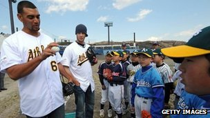 US US Major League Baseball team Oakland Athletics players Tyson Ross (L) and Evan Scribner (2nd L) conduct a baseball skills clinic for Ishinomaki youths during a visit to the Ishinomaki Municipality in March