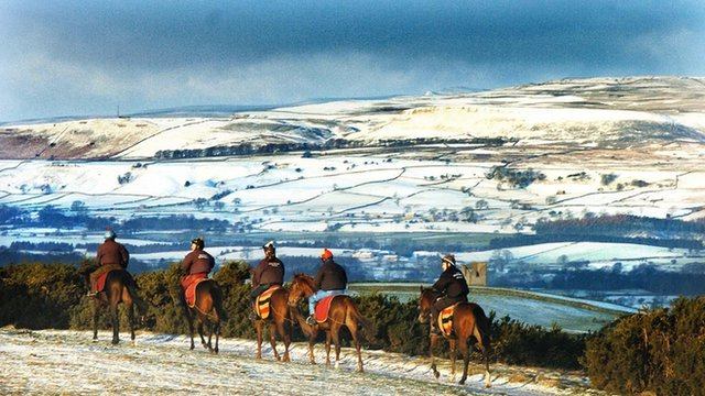 Snow covered landscape with jockeys training