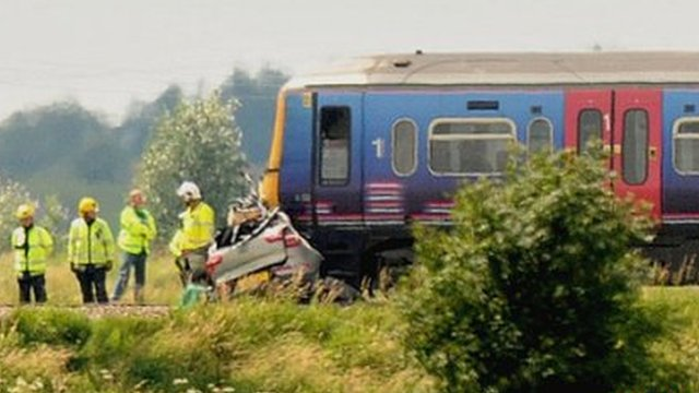 Car under front of train following crash at crossing