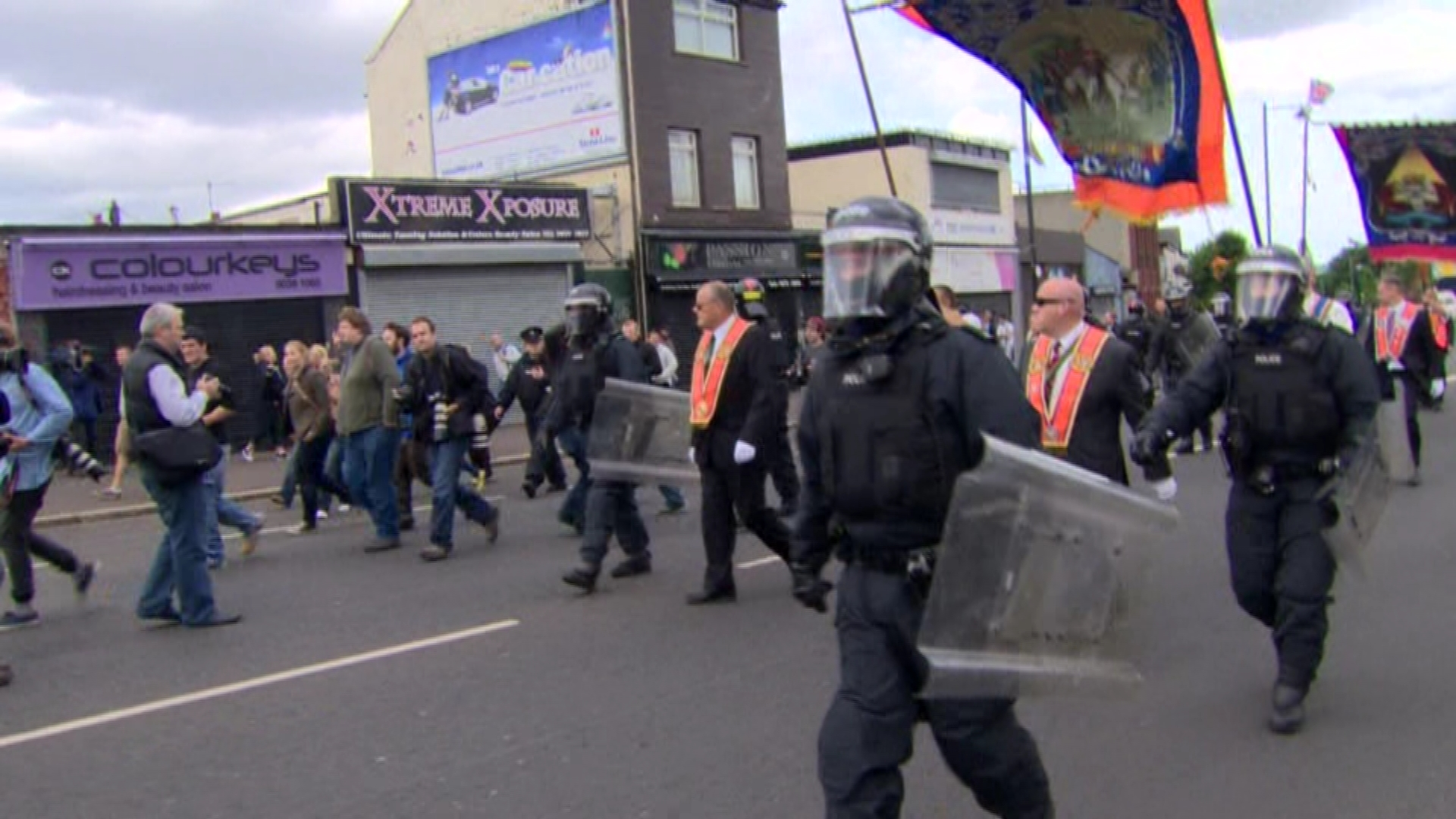 Orangemen walk past Ardoyne shops
