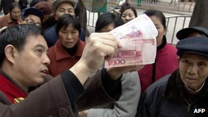 A bank employee shows customers on the street discrepancies between a real and a fake 100 Renminbi note.
