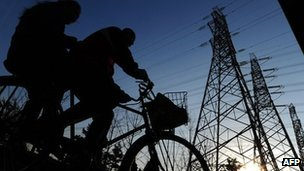 Chinese locals cycle past electricity cables