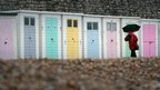 A woman walks past empty beach huts as people wait for the Olympic Flame to be carried around The Cobb in Lyme Regis, 12 July 2012