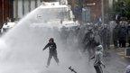 Rioter in water cannon stream