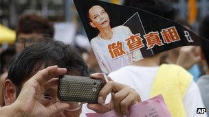 A man holding a flag with picture of Chinese activist Li Wangyang during a pro-democracy protest march in Hong Kong, 1 July, 2012