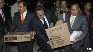 Leftist leaders carry boxes of documents the Federal Electoral Institute to back up their claim