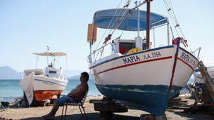 Man sits in shade of boat on Greek island.