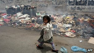 A girl walks past a pile of rubbish in Sanaa. Photo: 10 July 2012