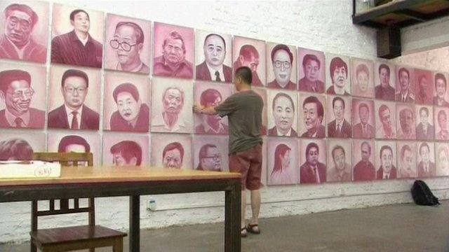 Beijing artist Zhang Bingjian hanging a portrait of a corrupt official in his &#039;Hall of Fame&#039;