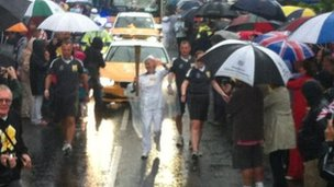Lesley Cook runs with the Olympic flame through Lymington