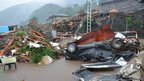 A destroyed car lies near collapsed houses after a landslide caused by heavy rains in Minamiaso town, Kumamoto prefecture.