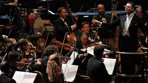 John Wilson (r) conducts his orchestra at the My Fair Lady Prom. © BBC/Chris Christodoulou