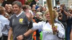 Susan Boalch carries the Olympic flame through St Peter Port in Guernsey